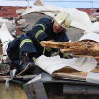 Hasič odsekává část střechy, kterou utrhl silný vítr. Ilustrační foto.