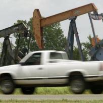 Auto projíždí kolem ropného vrtu u městečka Van v americkém státě Texas.