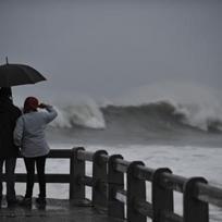Pár lidí pozoruje mořské vlny při vichřici na pobřeží. Ilustrační foto.