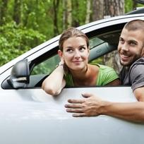 Mladý pár za volantem automobilu - ilustrační foto