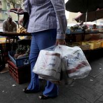 Ilustrační foto - Žena nese zakoupený toaletní papír na tržišti ve venezuelském městě Caracas.