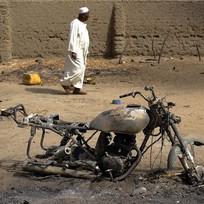 Muž míjí ohořelý motocykl ve vesnici zničené islámskými radikály ze skupiny Boko Haram. Ilustrační foto.