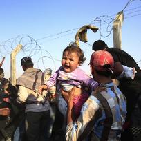 Ilustrační foto - Syrští uprchlíci přelézají plot na hranicích s Tureckem