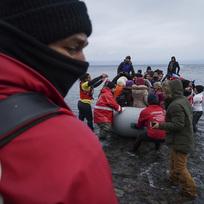 Příslušníci Červeného kříže pomáhají migrantům, kteří v člunu dorazili z Turecka na pobřeží řeckého ostrova Lesbos.
