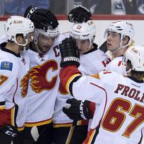 Český hokejista Michael Frolík se raduje s e svými spoluhráči z týmu Calgyra Flames.
