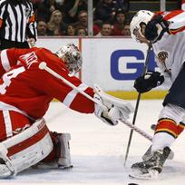 Brankář Detroitu Red Wings Petr Mrázek (vlevo) zasahuje před hráčem Floridy Panthers Loganem Shawem.
