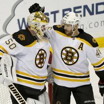Hokejista Bostonu Bruins David Krejčí (vpravo) gratuluje brankáři Jonasi Gustavssonovi k výhře nad Minnesotou 4:2.
