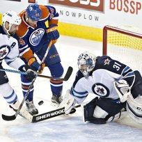 Český brankář týmu Winnipeg Jets Ondřej Pavelec likviduje šanci Zacka Kassiana z týmu Edmonton Oilers. Vlevo obránce Mark Stuart.