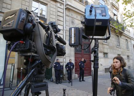 Francouzští policisté a televizní reportéři před rezidencí, kde mají byt americká celebrita Kim Kardashianová a její manžel Kanye West v Paříži.