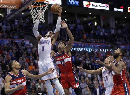 Basketbalista Oklahoma City  Russell Westbrook (v bílém) skóruje v utkání NBA, uprostřed Kelly Oubre Jr. zWashingtonu.