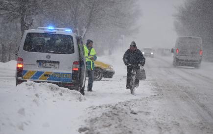 Policie uzavřela kvůli počasí cestu pro kamiony mezi Ostravicí a Bílou v Moravskoslezském kraji. Na snímku z 1. února míjí cyklista policejní hlídku, která v Ostravici kontroluje řidiče kamionů.