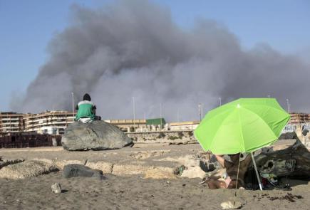 Lidé na pláži sledují lesní požár poblíž Říma.