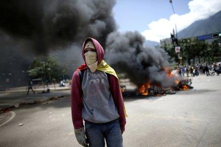 Demonstrant u hořících trosek motocyklů zapálených při střetech protivládních demonstrantů s policií ve venezuelském Caracasu.