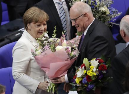 Angela Merkelová přijímá květiny od šéfa poslanců CDU Volkera Kaudera poté, co byla znovu zvolena německou kancléřkou.