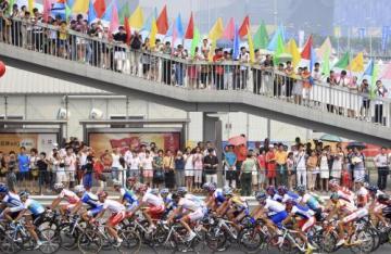 Diváci v Pekingu sledují peloton cyklistů.