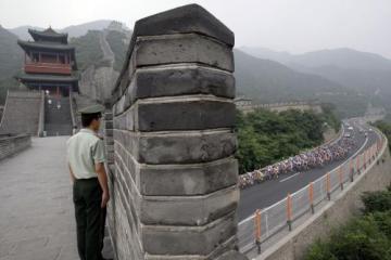 Peloton cyklistů projíždí kolem Velké čínské zdi.