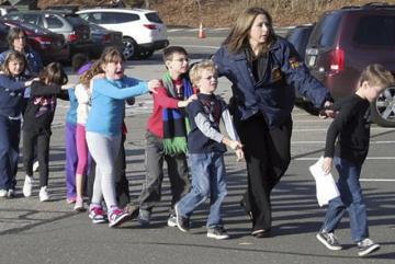 Při střelbě ve škole ve městě Newtown v americkém státě Connecticut bylo dnes zastřeleno několik lidí, včetně dětí. Napsal to na své webové stránce místní list Harftord Courant s odvoláním na blíže neupřesněné zdroje. Na snímku děti pod dozorem policistky opuští okolí školy.