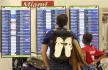 Ilustrační foto - Lidé sledují tabuli s odlety letadel na letišti v Miami na FLoridě.
