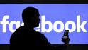 Ilustrační foto - Muž s mobilním telefonem před logem společnosti Facebook - ilustrační foto.
