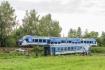 Vlak projíždí 6. srpna 2021 po opravené trati u Milavče na Domažlicku, kde 4. srpna při tragické srážce dvou vlaků zahynuli tři lidé.V popředí je zničený vagon, odstavený po nehodě z trati na přilehlou louku.