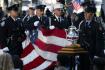 Památeční vlajka je přinášena na pódium během pietyna památku obětí teroristických útoků 11. září 2001.
