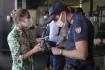 Italský policista kontroluje mobilní telefon cestující na nádraží v Miláně.Itálie se nejspíš stane první evropskou zemí, která bude po všech zaměstnancích požadovat, aby se prokazovali covidovými certifikáty.