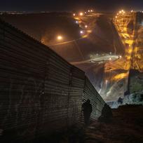 Migranti hledají místo, kde překonat plot na hranici mezi Mexikem a USA.