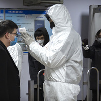 Ilustrační foto - Muž v ochranném obleku měří 26. ledna 2020 teplotu cestujícímu v metru v Pekingu.