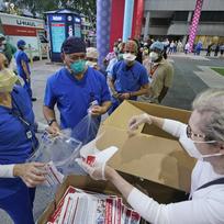 Rhonda Rolandová Shearerová, zakladatelka newyorské neziskové organizace Cut Red Tape 4 Heroes, pomáhá rozdávat ochranné pomůcky zdravotníkům u Jacksonovy nemocnice v Miami, 22. září 2020.
