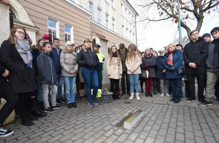 Před Základní školou v Hálkově ulici v Olomouci, kde se za druhé světové války nacházelo shromaždiště Židů určených k transportu, byl 14. listopadu k uctění jejich památky položen více než půlmetrový kámen zvaný Stolperschwelle. Na snímku žáci devátých tříd školy přihlížejí umístění kamene do dlažby chodníku.