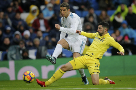 Fotbalista Realu Madrid Cristiano Ronaldo (vlevo) střílí přes hráče Villarrealu Álvara Gonzáleze.