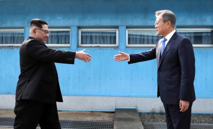 Severokorejský vůdce Kim Čong-un (vlevo) a jihokorejský prezident Mun Če-in se zdraví na hraniční čáře mezi oběma zeměmi v obci Pchanmundžom.