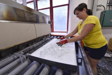 Sklárna Janštejn na Jihlavsku začíná vyrábět designové sklo ze střepů, které byly doposud jen odpadem z tradiční ruční výroby skleněných dílů ke svítidlům. Na snímku z 2. července je pracovnice u zapékací pece na skleněné desky ze střepů.