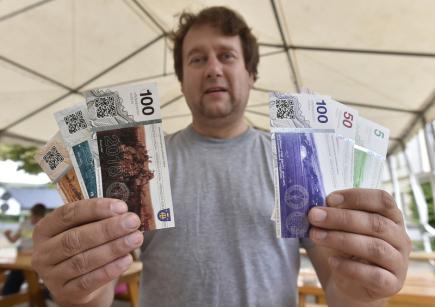 Starosta obce Křižánky na Žďársku Jan Sedláček ukazuje 9. července novou (vlevo) a starou edici místní měny (vpravo), kterou obec zavedla, aby podpořila zdejší podnikání. Křižánecká koruna má v poměru ke Koruně české hodnotu jedna ku jedné, bankovky zdobené místními motivy mají hodnotu 100, 50 a pět korun. Lidé s nimi mohou platit třeba na obecním úřadě, v obchodě nebo u kadeřnice. Majitelé trvale obydlených domů dostávají v lokální měně náhradu za část vybrané daně z nemovitostí.