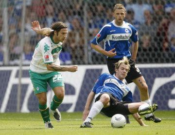 Fotbalista Brém Torsten Frings (vlevo) a hráč Bielefeldu Thorben Marx (vpravo), vzadu přihlíží jeho spoluhráč Radim Kučera.