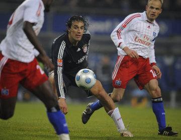 Fotbalista Bayernu Mnichov Luca Toni (uprostřed) mezti hráči Hamburku Guyem Demelem (vlevo) a Davidem Jarolímem.