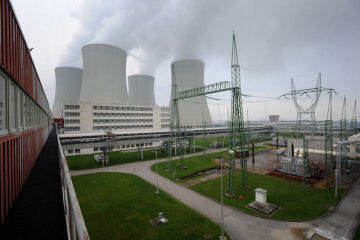 Pohled na chladicí věže a rozvod elekřiny od turbosoustrojí prvního bloku jaderné elektrárny Temelín.