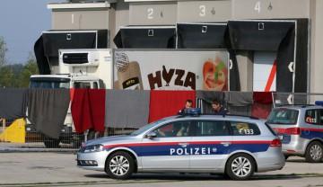 Policie vyprošťuje těla běženců z chladírenského vozu v prostoru někdejší pohraniční veterinární stanice (snímek z 27. srpna 2015).