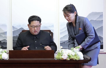 Severokorejský vůdce Kim Čong-un se podepisuje do knihy hostů během zahájení summitu v Mírovém domě v jihokorejském Pchanmundžomu 27. dubna 2018. Vpravo sestra lídra KLDR Kim Jo-čong.