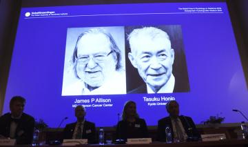Letošní Nobelovu cenu za fyziologii a lékařství získali Američan James P. Allison (na projekci vlevo) a Japonec Tasuku Hondžó (vpravo) za vývoj speciální imunologické léčby rakoviny.
