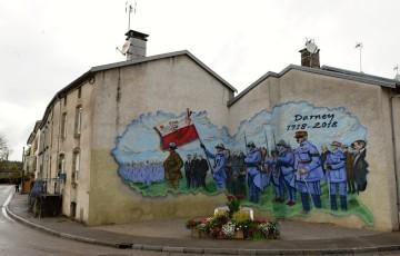 Graffitti (na snímku z 21. září 2018) připomíná na nároží ve francouzském městečku Darney událost z 30. června 1918. Českoslovenští legionáři tam z rukou francouzského prezidenta Raymonda Poincarého tehdy slavnostně převzali vlajku, darovanou městem Paříží.