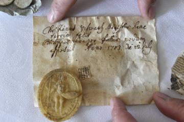 Voskovou medaili, kterou objevili dělníci při opravách střechy kostela v Morkovicích-Slížanech na Kroměřížsku, ukazuje farář Jan Ston při setkání s novináři 22. října 2018. V báni na opravované střeše našli stavbaři několik listin, dvě mince a dvě medaile z 18. století.