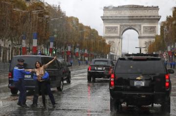 Francouzští policisté chytají aktivistku hnutí Femen, která pronikla ke koloně amerického prezidenta Donalda Trumpa.