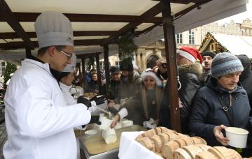 Starosta Prahy 1 Pavel Čižinský (vlevo) rozléval 24. prosince 2018 na Staroměstském náměstí v Praze vánoční rybí polévku.