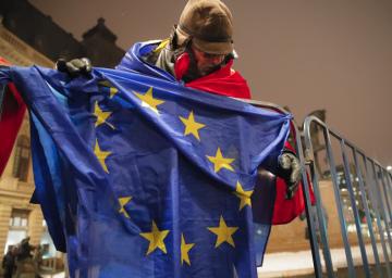 Demonstrant s vlajkou EU před koncertní síní v rumunské Bukurešti.
