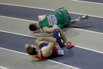 Český atlet Jan Tesař (dole) leží na zemi po pádu v rozběhu na 400 m na halovém MS V Glasgow. Nahoře je Cillin Greene z Irska.