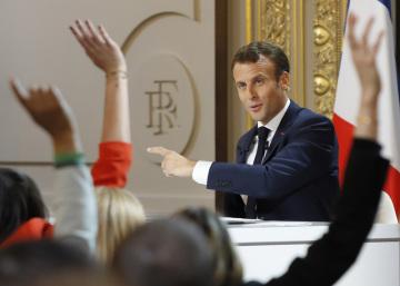 Francouzský prezident Emmanuel Macron během mimořádného vystoupení v Elysejském paláci. v Popředí zástupci médií.
