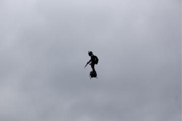 """""""Létající muž"""" na futuristickém zařízení zvaném Flyboard Air během tradiční vojenské přehlídky v Paříži u příležitosti dnešních oslav francouzského státního svátku . Je to zvláštní vznášedlo podobné dronu a vybavené podle AFP několika motory. Pilot na zařízení během letu stojí."""
