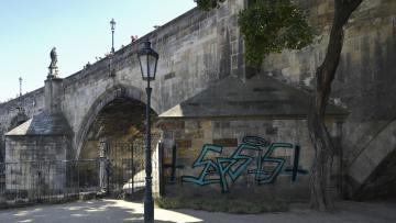 Policie zadržela dva cizince ve věku 23 a 30 let, kteří 15. července 2019 večer posprejovali jeden z pilířů Karlova mostu v Praze (na snímku z 16. července 2019). Podezřívá je z poškození cizí věci, škoda zatím nebyla vyčíslena. Hrozí jim až tři roky vězení.