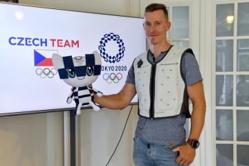 Dráhový cyklista Tomáš Bábek oblečený do speciální chladivé vesty pro sportovce pózuje s maskotem Miraitowou 18. července 2019 v Praze na setkání s novináři na téma olympijské hry v Tokiu, do nichž bude 24. července zbývat rok.